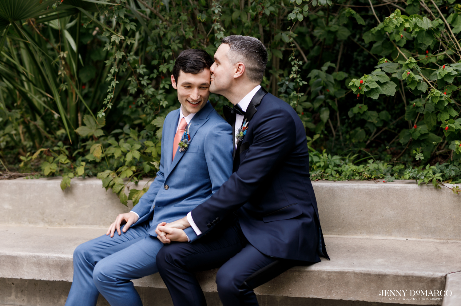 Grooms sitting on bench while groom on right kisses the forehead of the groom on left