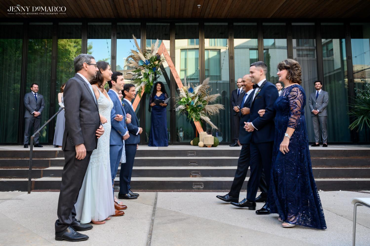Grooms and their families facing each other at the end of the aisles