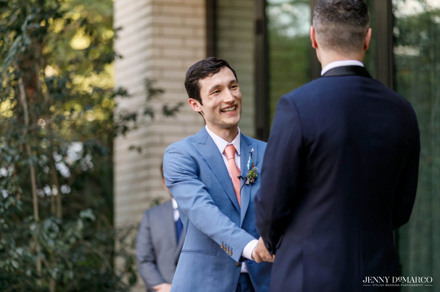 Groom laughing at spouse while holding hands
