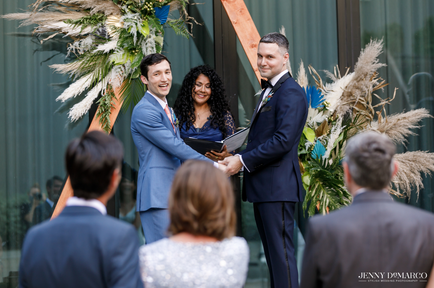 Grooms holding hands and smiling at parents before saying their vows