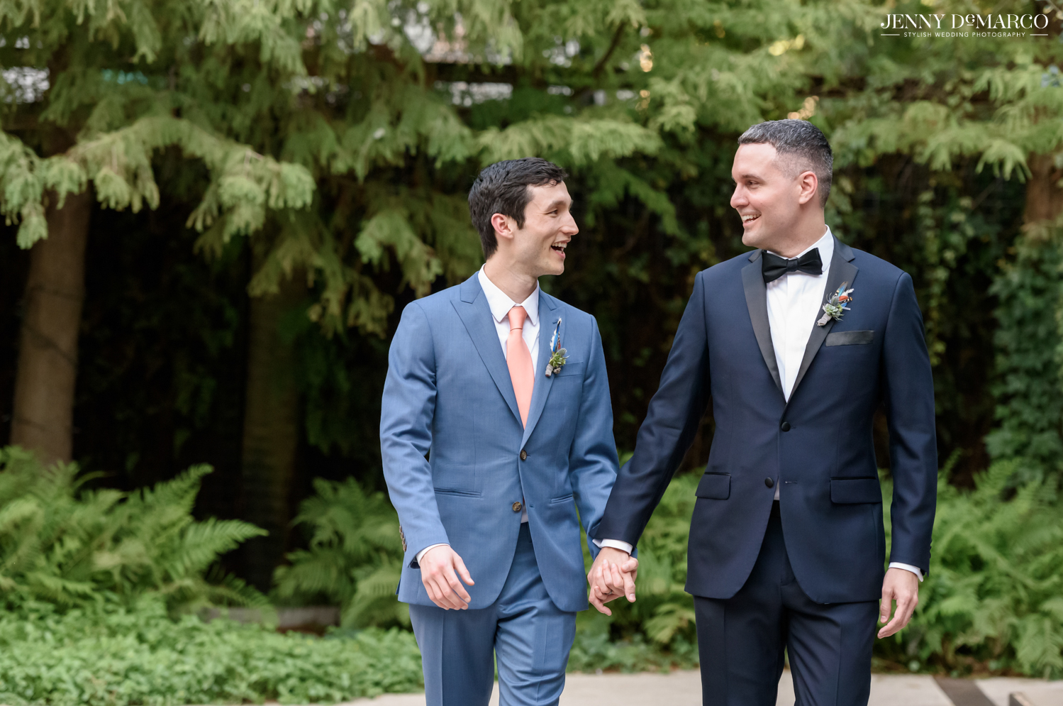 Grooms holding hands and laughing at each other while walking