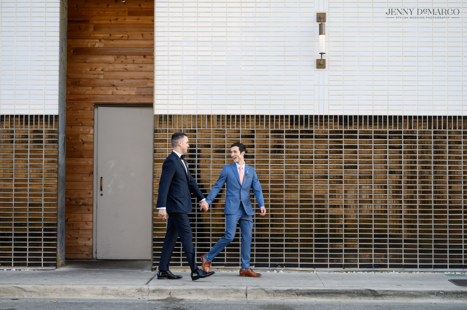 Grooms holding hands while walking on sidewalk and laughing
