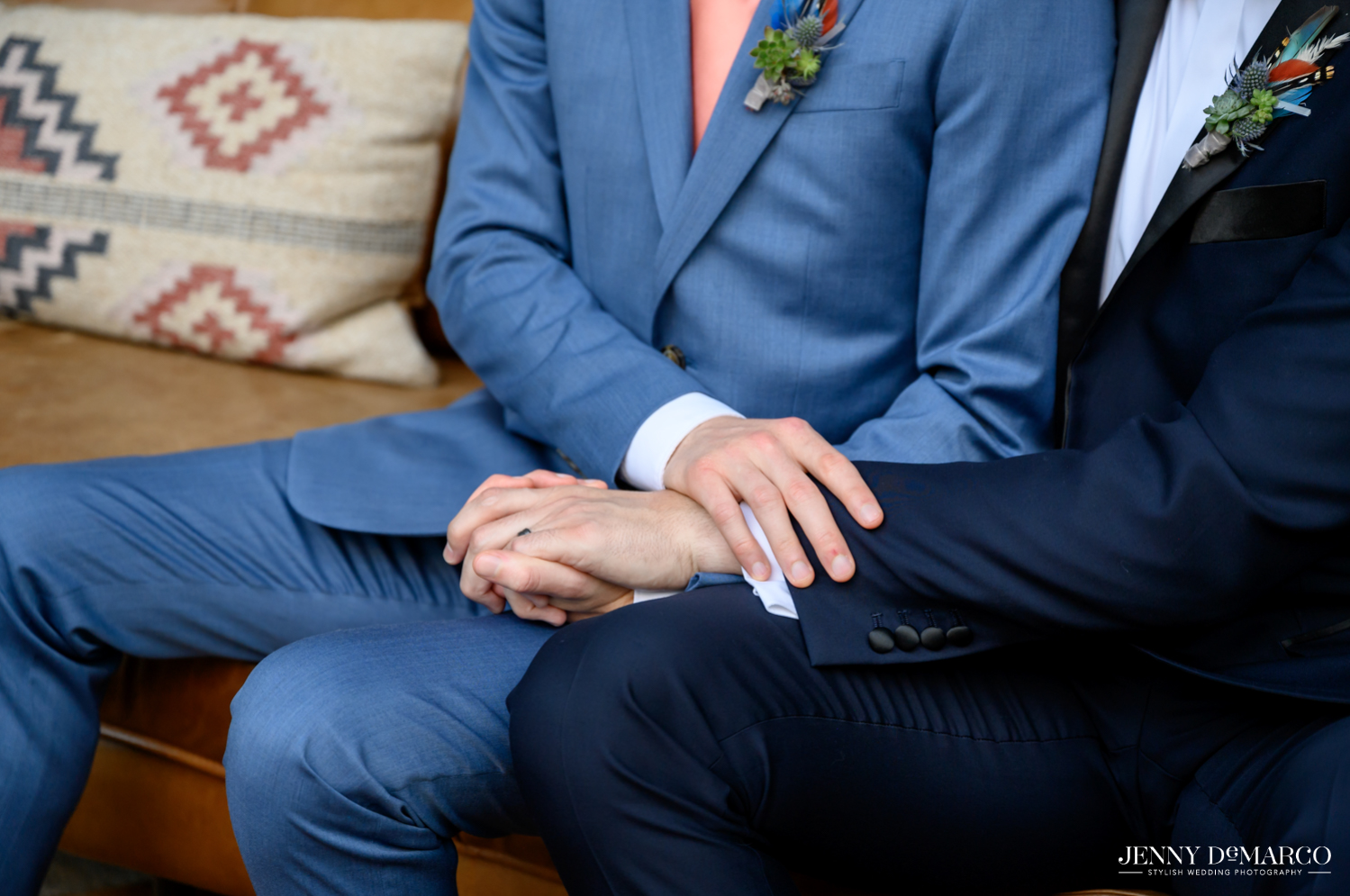 Close up of grooms sitting on couch and holding hands