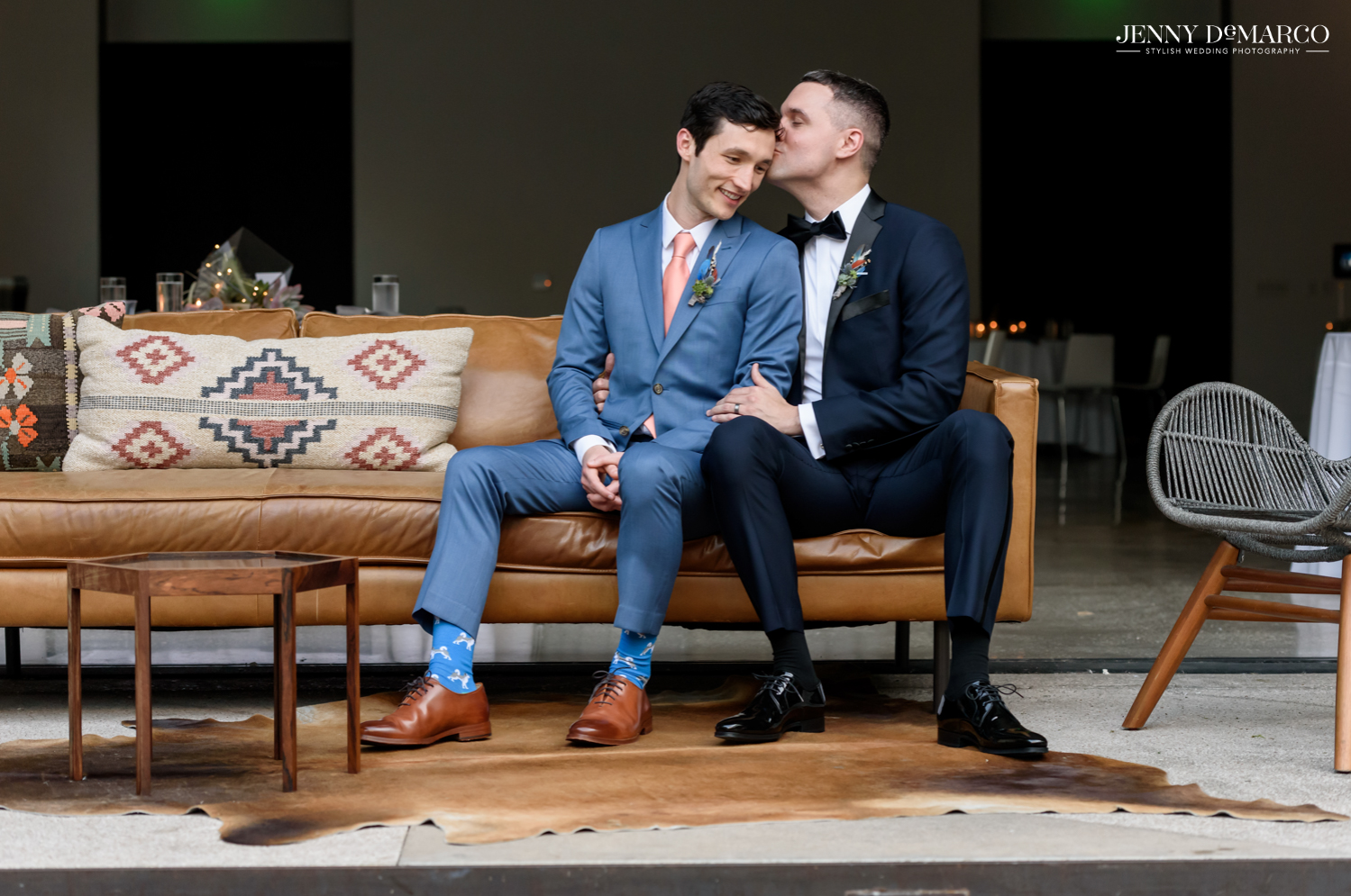 Grooms sitting on couch while groom on right kisses the forehead of groom on left