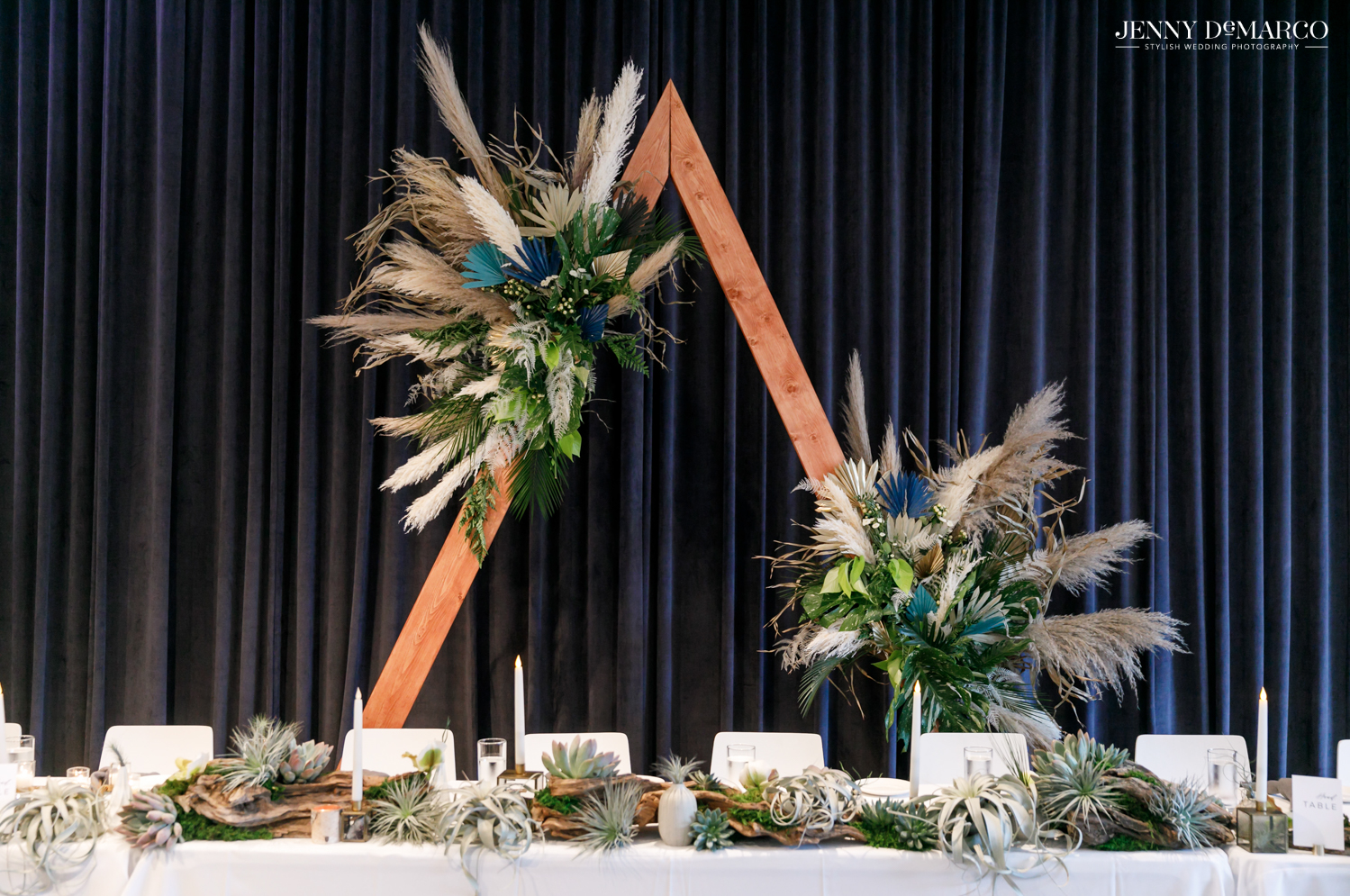 Reception decorations of wooden triangular piece with feathered detailing and important persons table