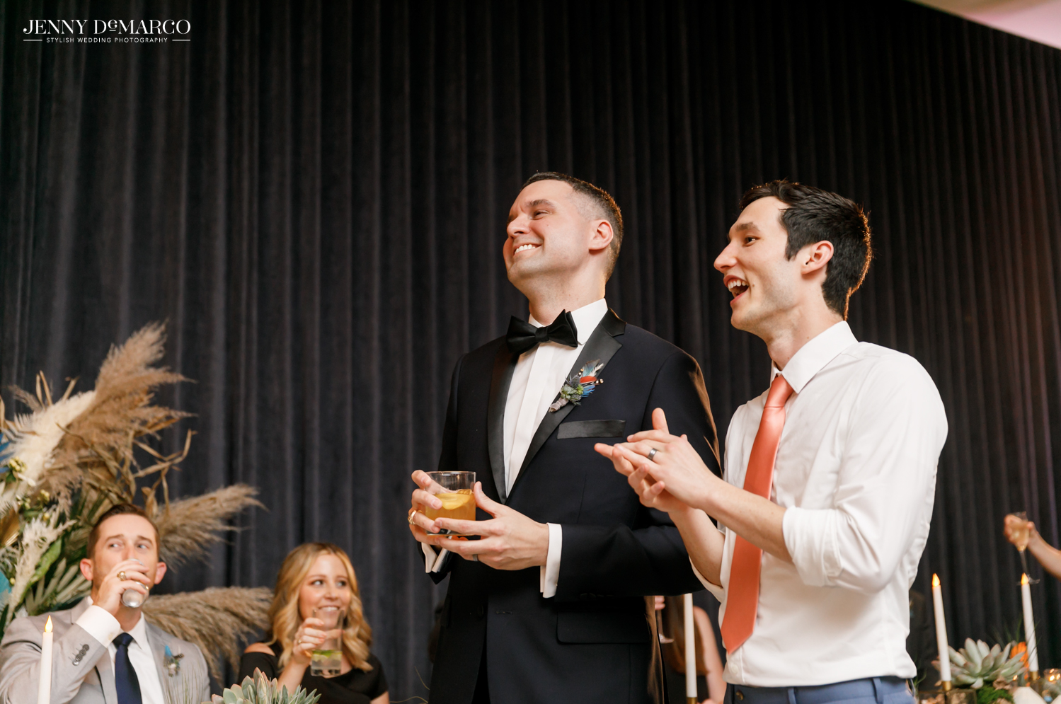 Grooms standing and laughing during reception