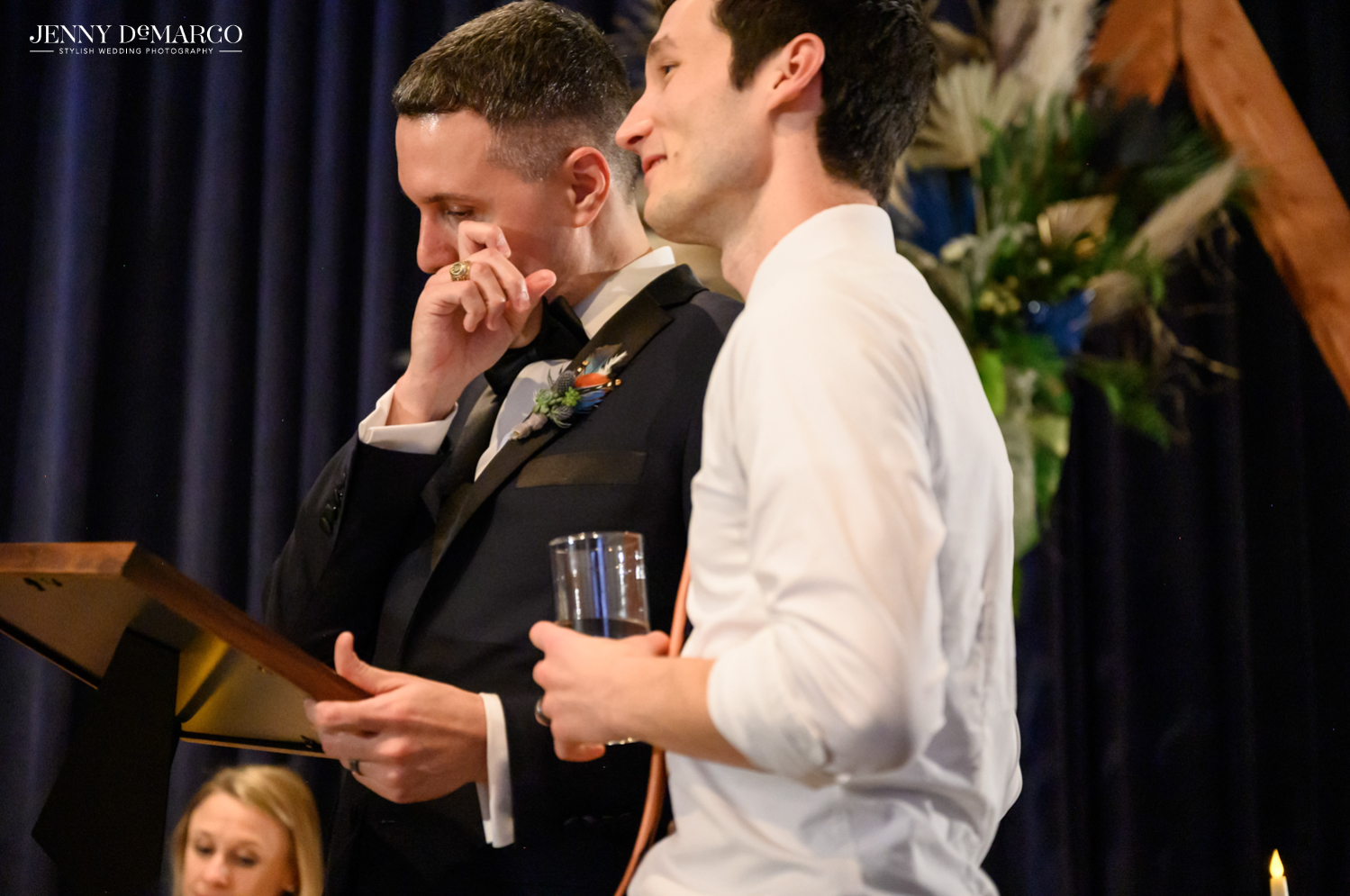 Grooms looking at framed gift and wiping a tear