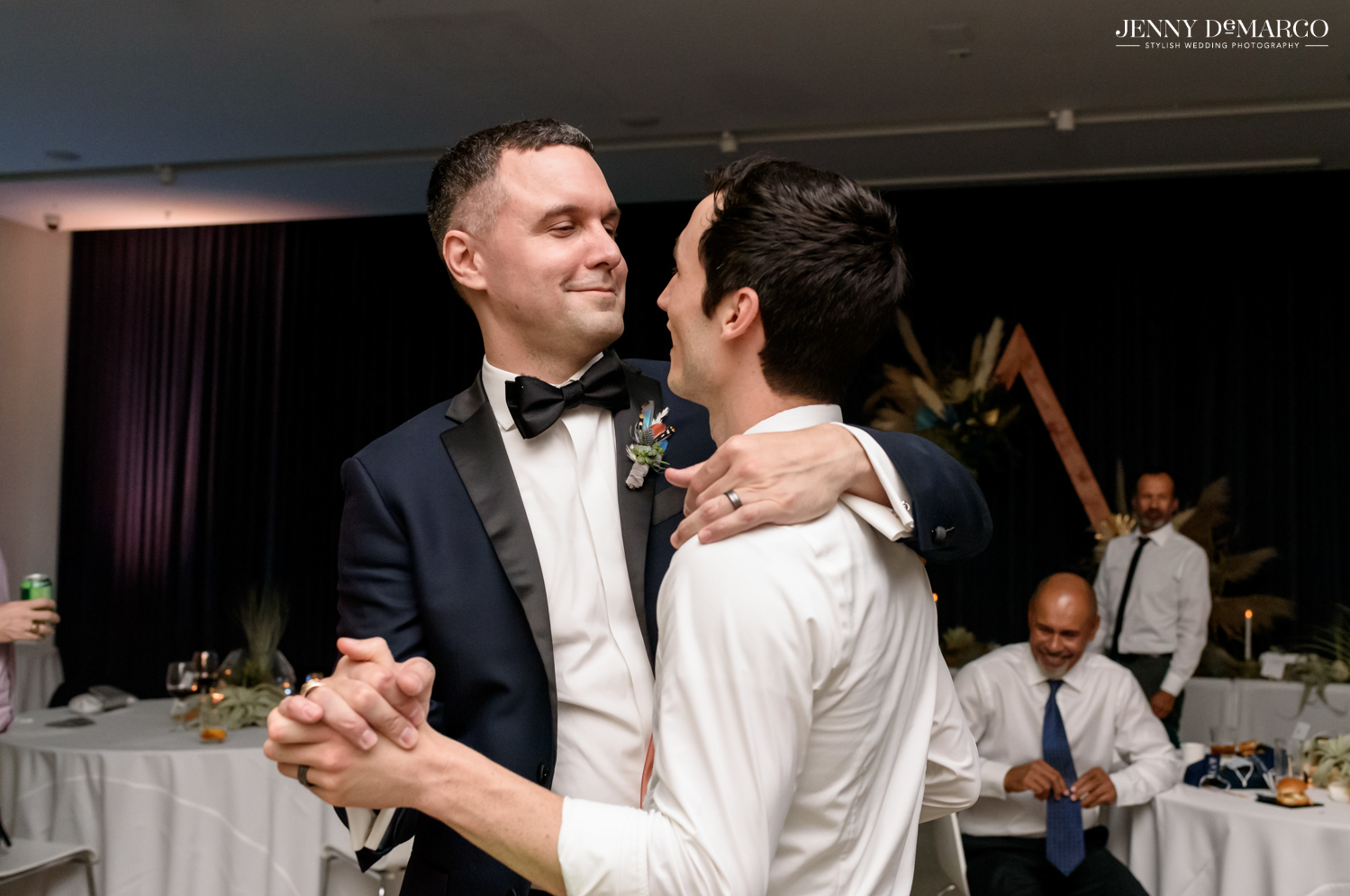 Grooms slow dancing during reception