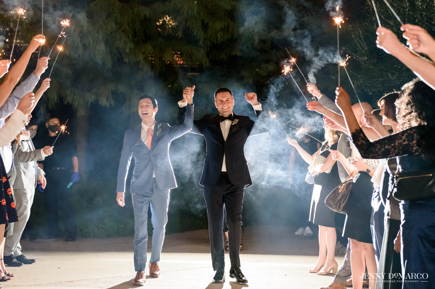 Grooms walking out while guests hold sparklers around them and cheer