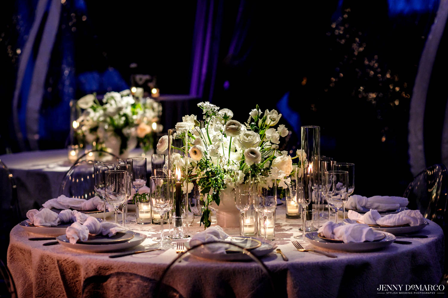 set dining table at evening with lit candles around the white floral arrangement in center