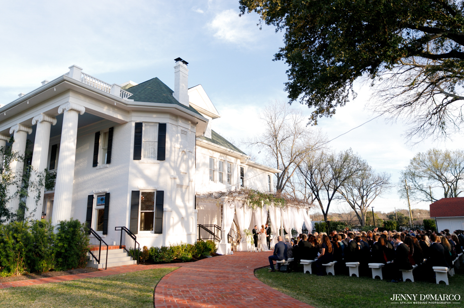 wide view of wedding ceremony under the woodbine mansion