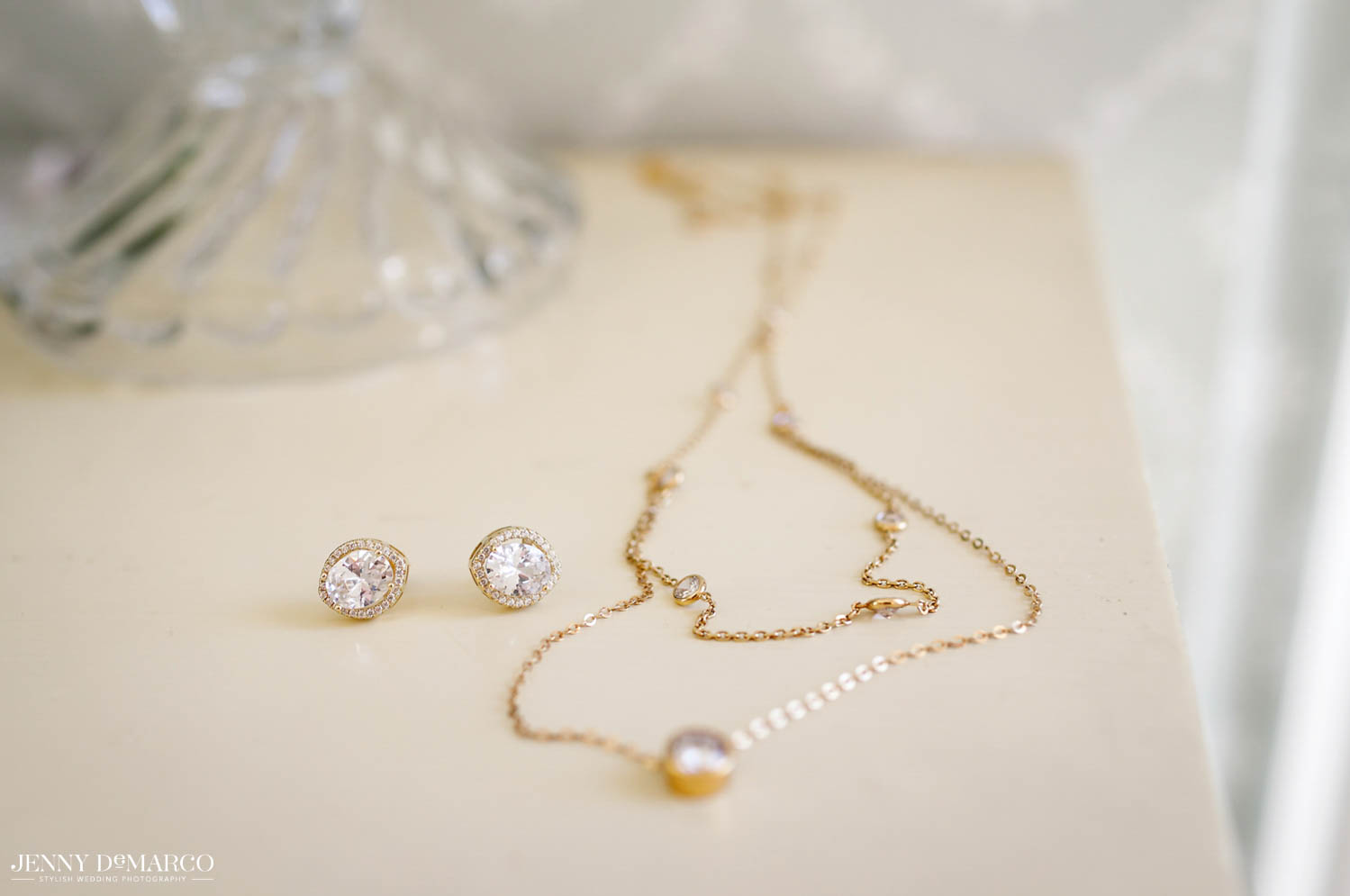 bride's stud diamond earring and gold necklace with diamond in the center