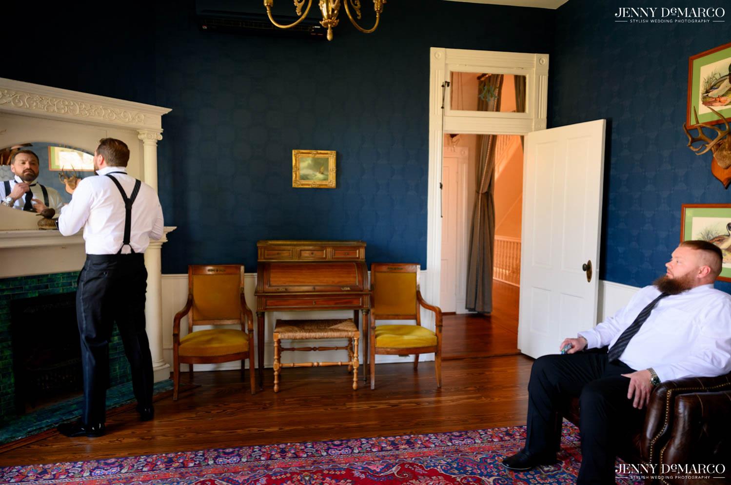 groom looking in mirror taking to his best man