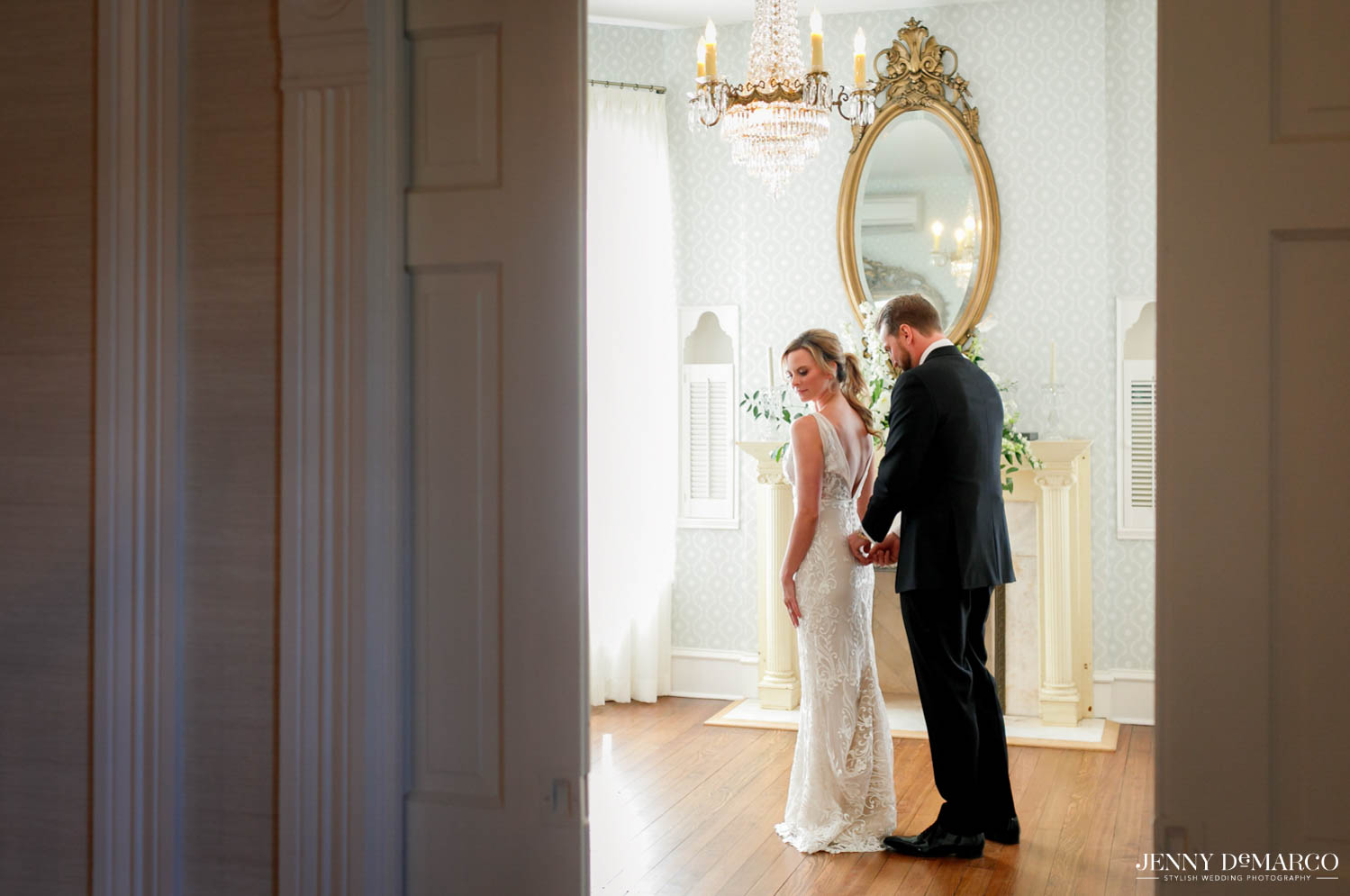 groom zipping the bride into her dress
