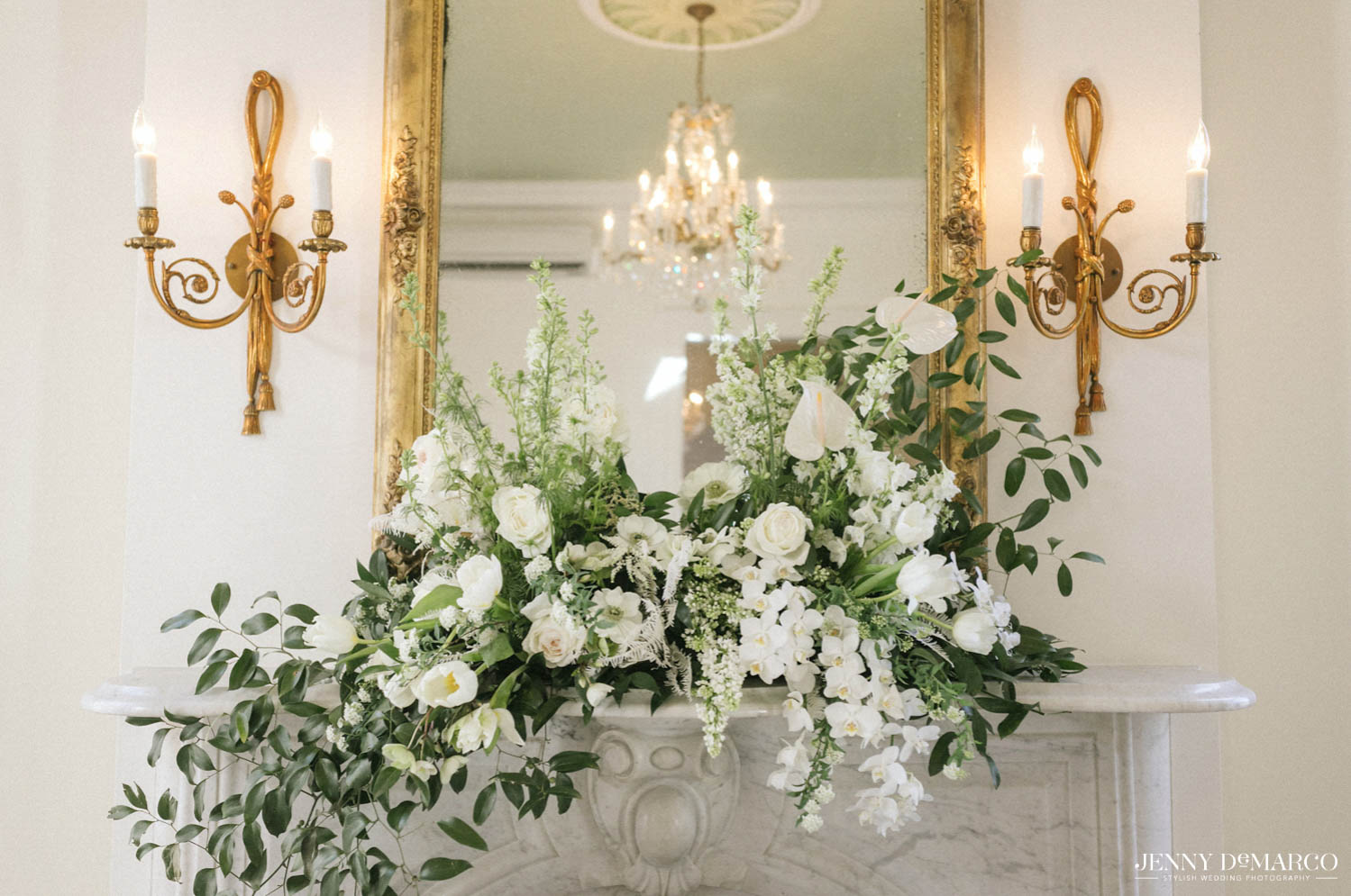 white floral arrangement in between two candles on top of a mantle