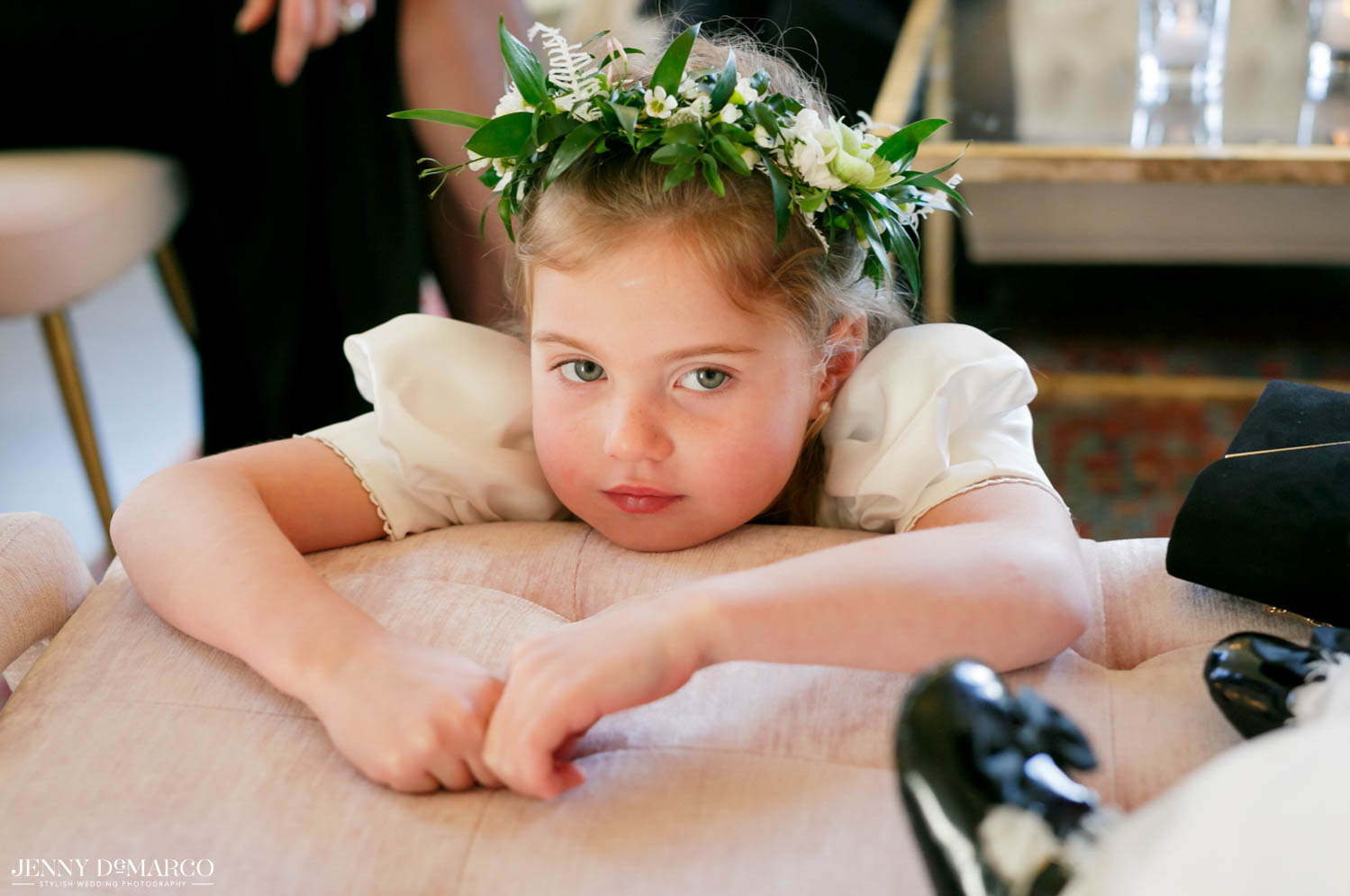 flower girl laying over chair with greenery in her hair