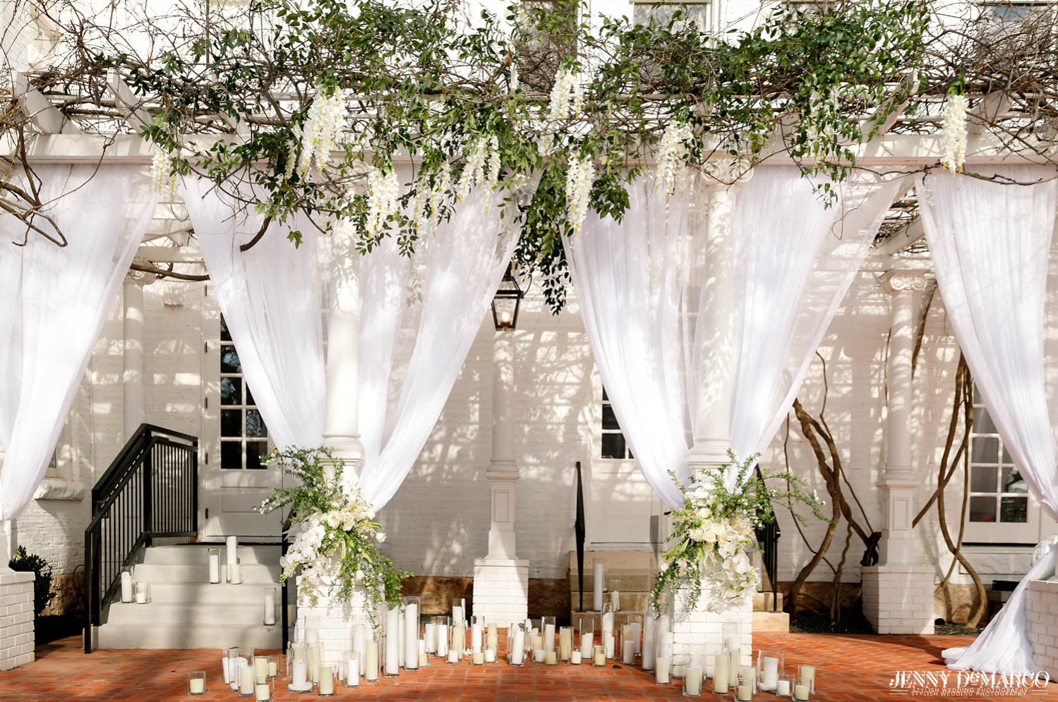 ceremony location with a  multitude of candles covering the floor and white drapes on the pillars of the mansion