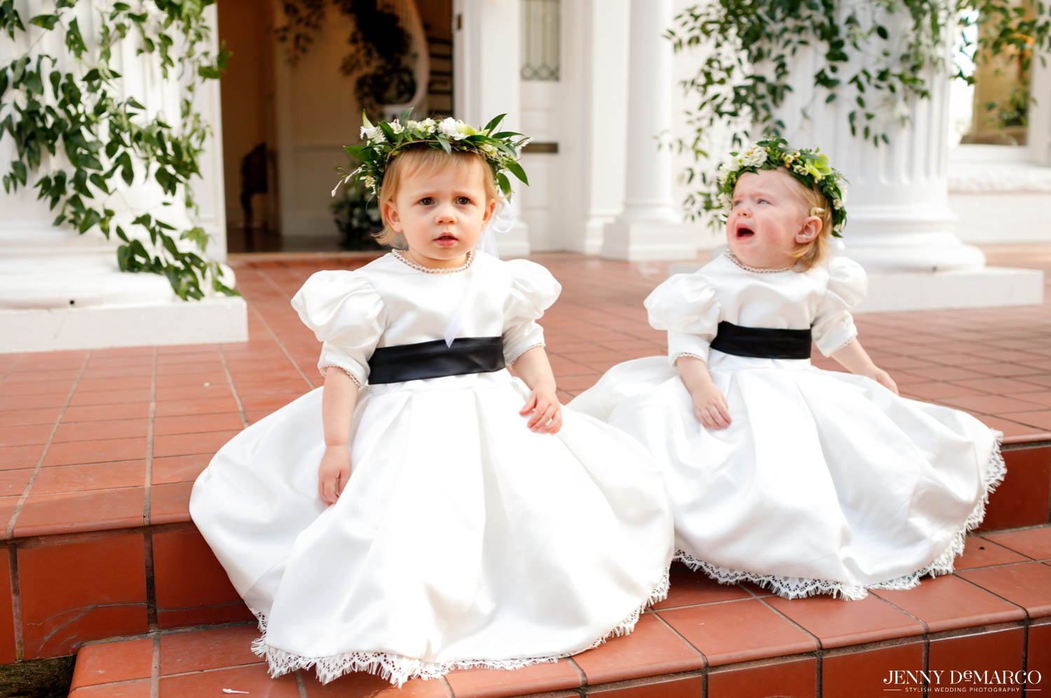 two baby girls sitting on steps of woodbine mansion before the ceremony