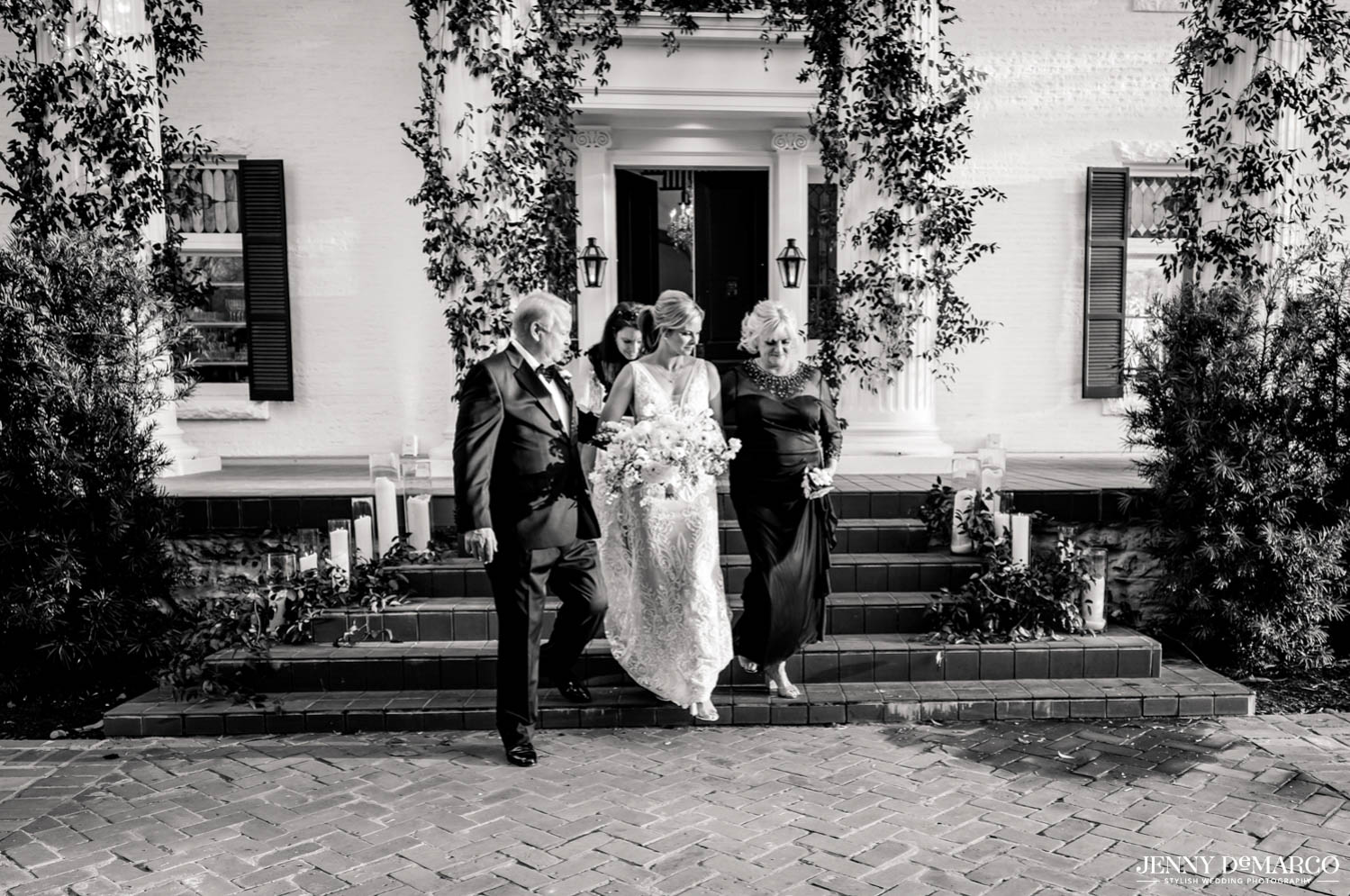 bride walking into the ceremony accompanied by father and family