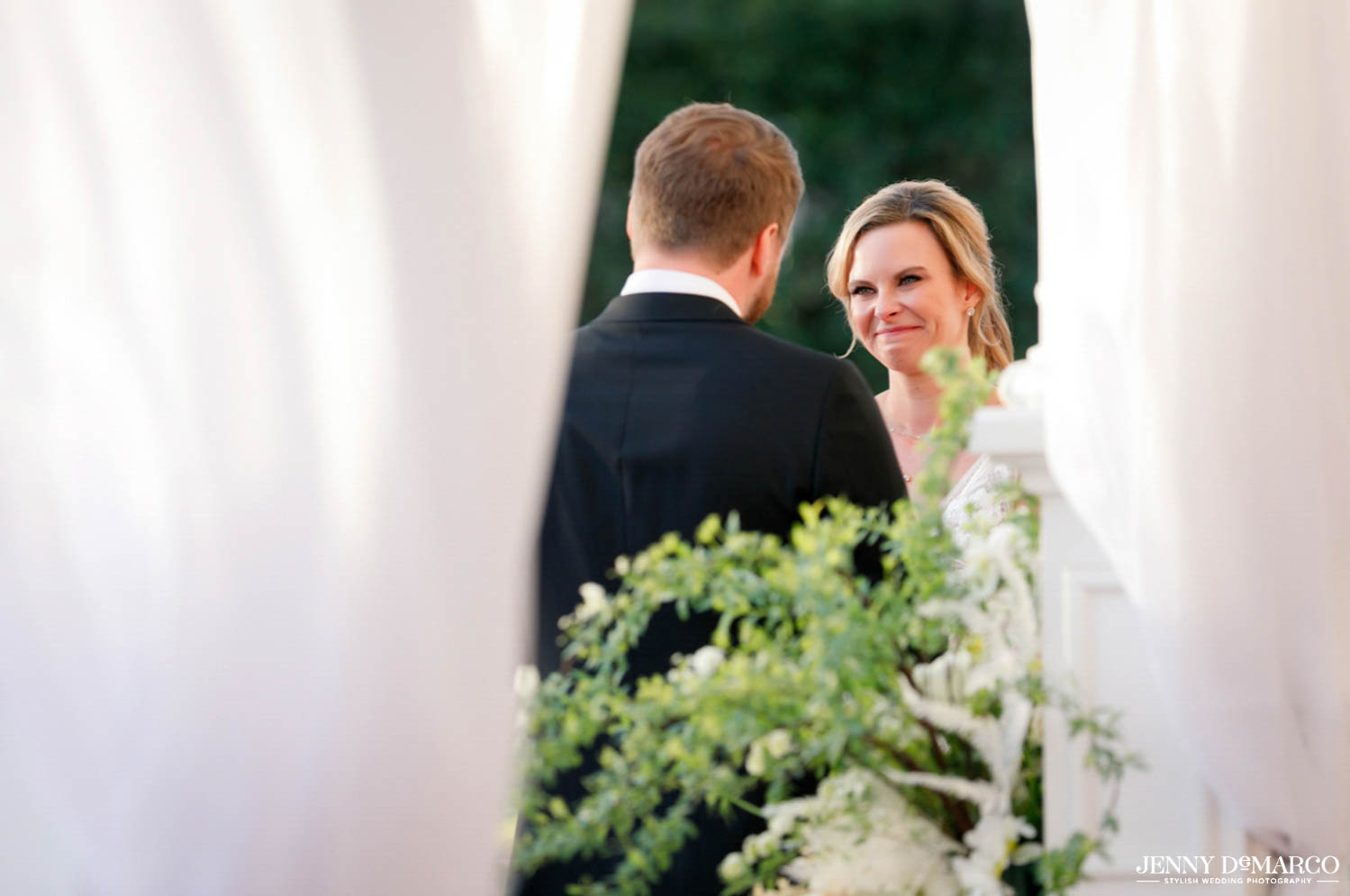 bride and groom smiling at each other in ceremony