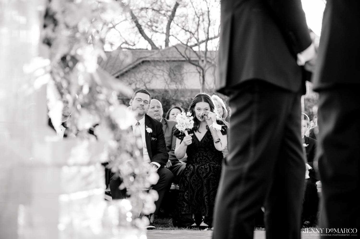 wedding guests during ceremony wiping her eyes