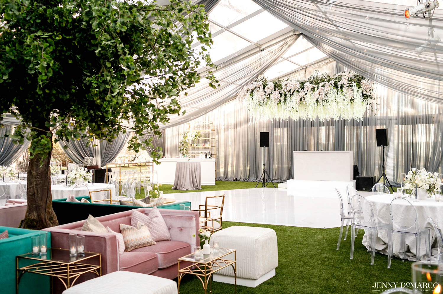 wedding reception tent with large hanging floral arrangement over dance floor and white decorated tables