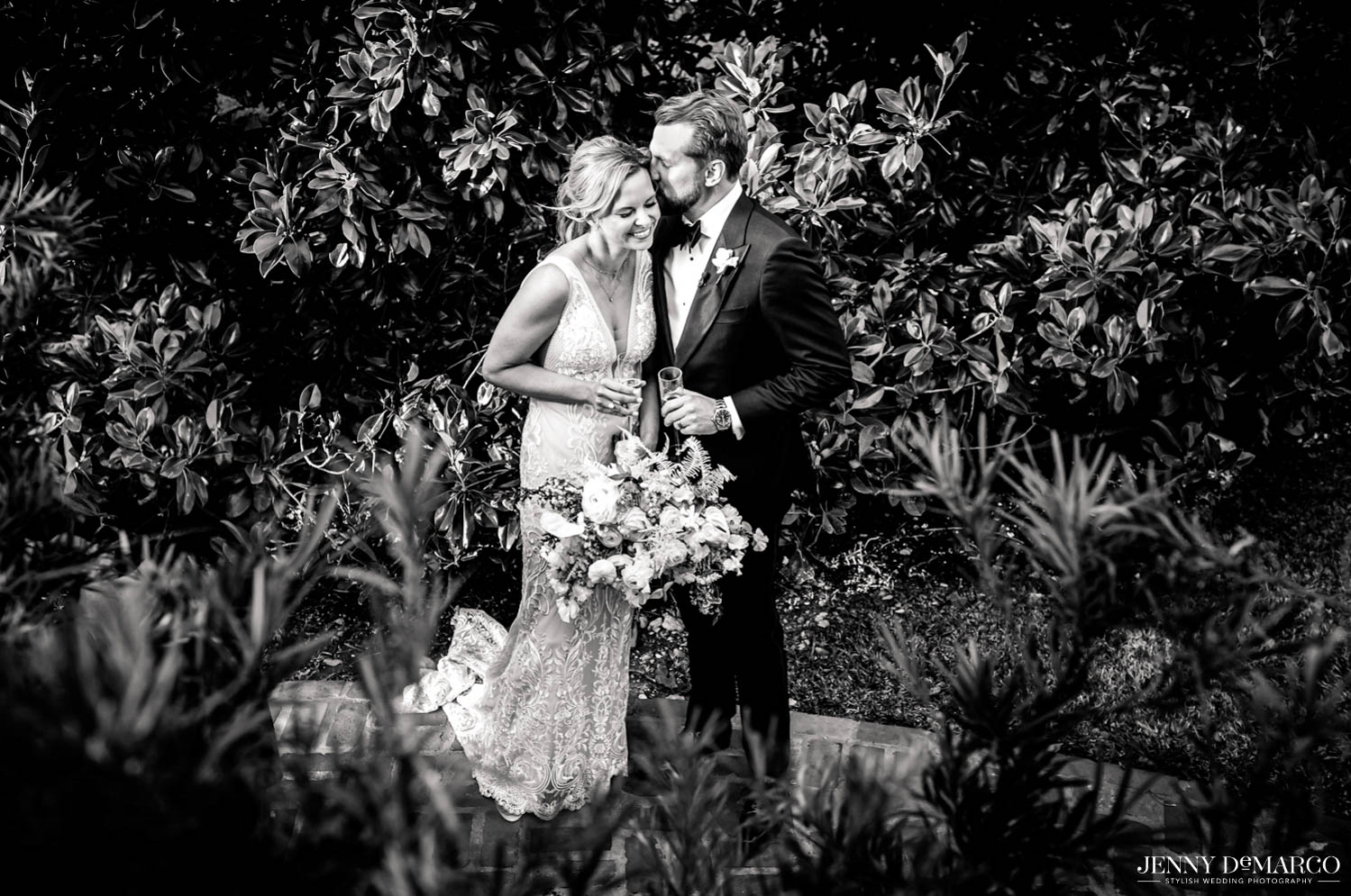 bride and groom behind greenery laughing and kissing