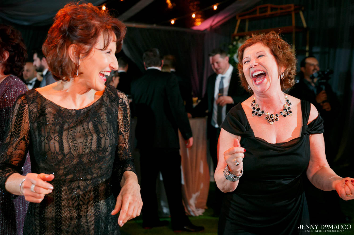 mother of bride laughing with friend and dancing