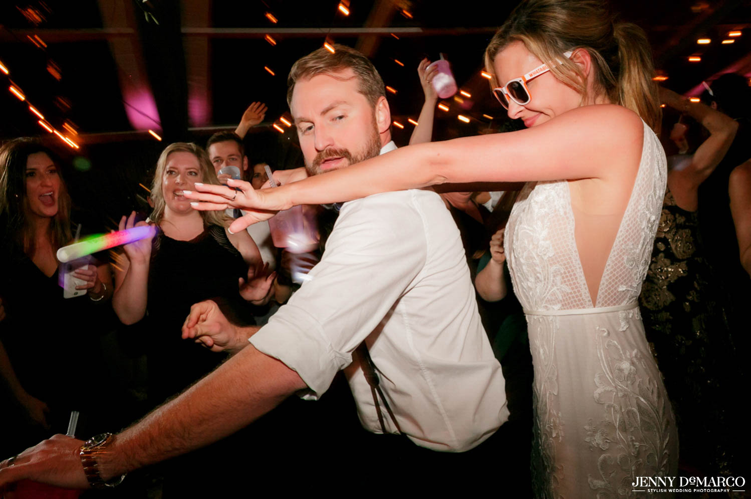 bride and groom dancing in middle of guest with glowsticks and sunglasses