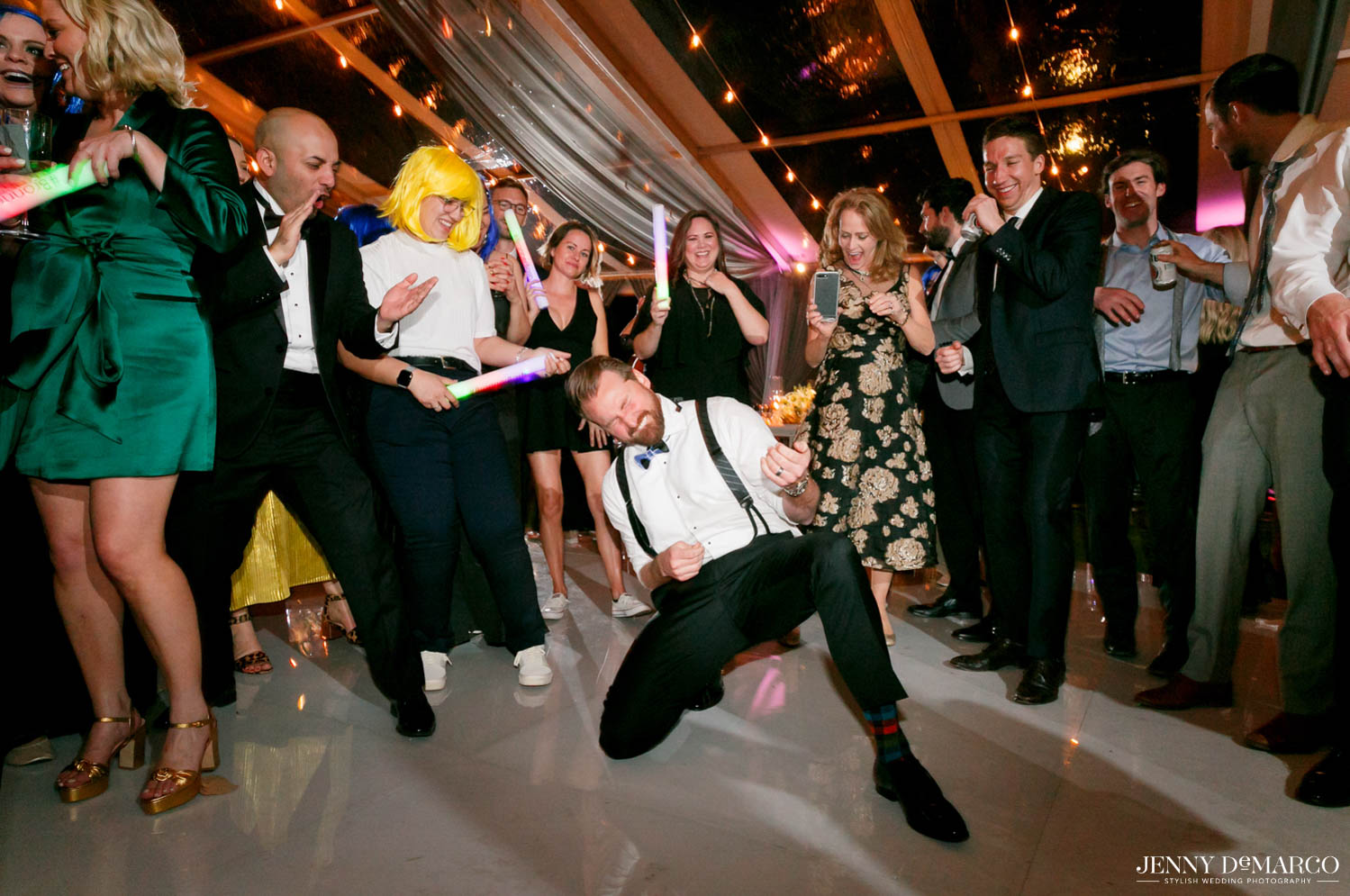 groom dancing in middle of crowd playing an air guitar