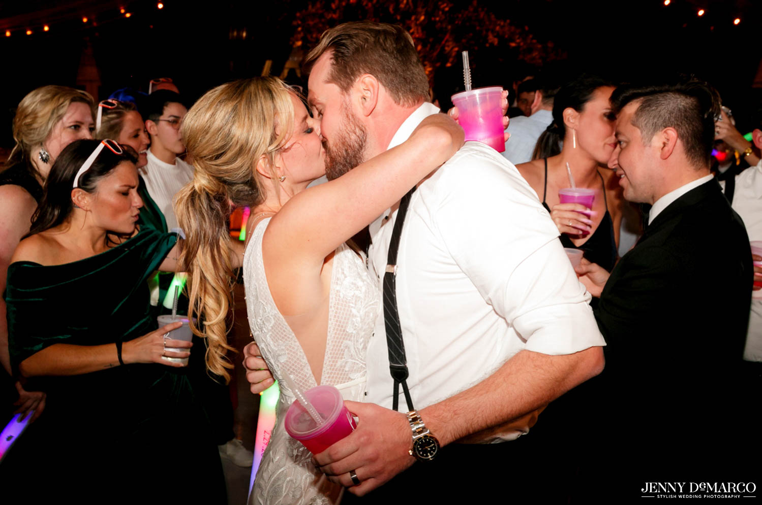 bride and groom kissing in middle of dance floor with guests dancing around