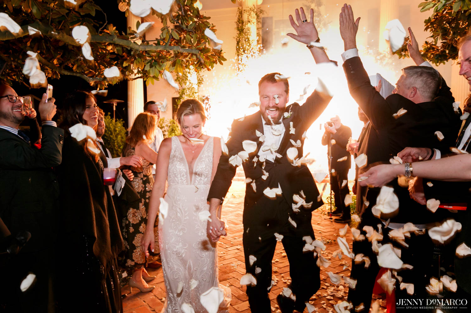 bride and groom making their final exit with roses and light explosion in background